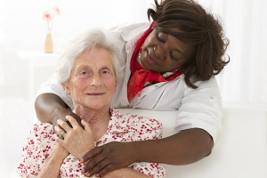 happy senior woman with friendly african american caregiver